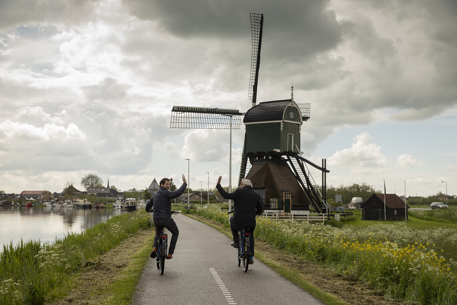 Gedeputeerde en wethouder op de fiets bij de molen in Meerkerk